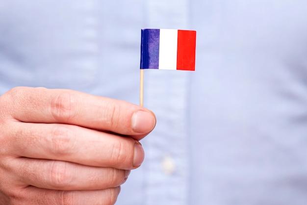Un homme tenant un drapeau en papier de la france sur un cure-dent en bois , concept photo