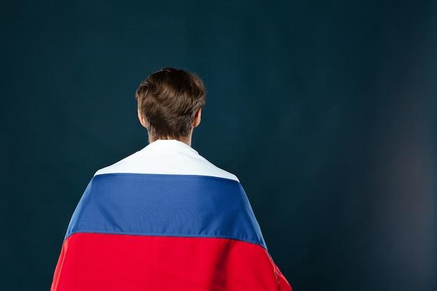 Homme tenant le drapeau de la russie sur le mur noir