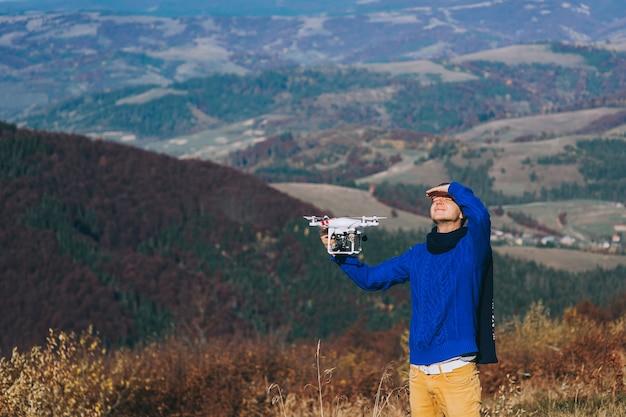 Homme tenant un drone pour la photographie aérienne. silhouette contre le ciel du coucher du soleil
