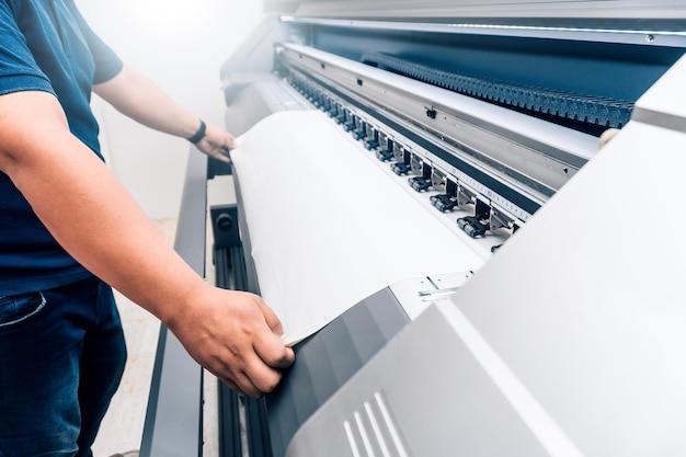 Homme tenant du matériel imprimable sur un traceur d'impression grand format