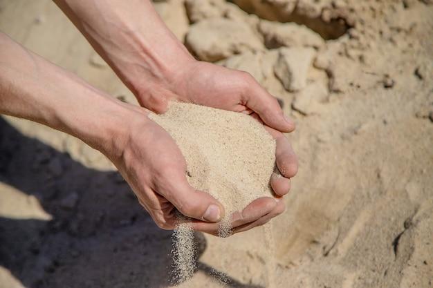 Homme tenant du sable dans ses mains