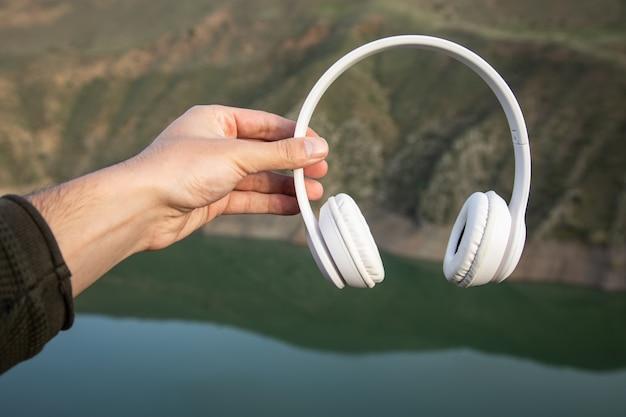 Homme tenant des écouteurs à la surface de la montagne. concept sonore de la nature