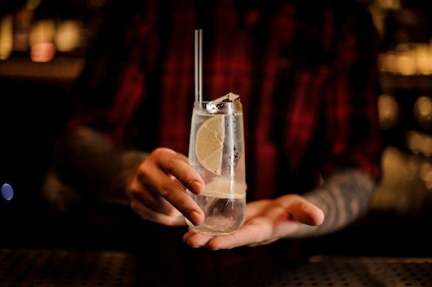 Homme tenant un élégant verre long drink rempli de cocktail tom collins