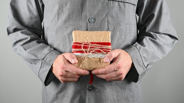 Homme tenant un emballage cadeau sur fond gris. photo de haute qualité