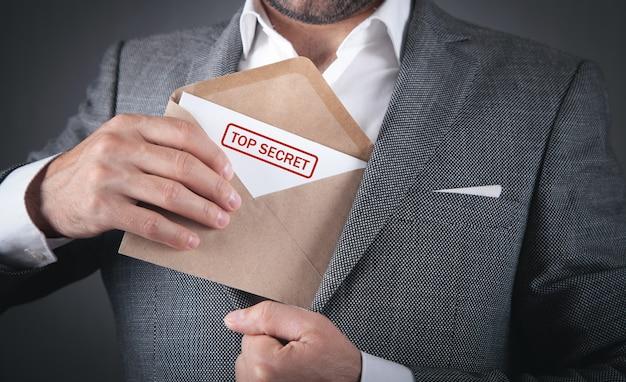 Homme tenant une enveloppe avec un cachet top secret.