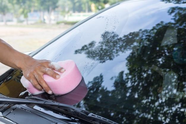 Homme tenant une éponge pour laver une voiture blanche