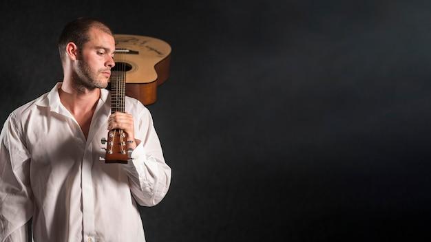 Homme tenant l'espace de copie de guitare acoustique