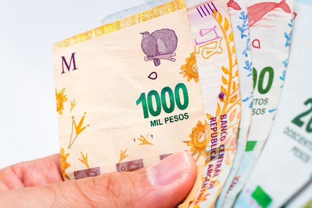 Un homme tenant des factures d'argent de l'argentine en photographie rapprochée