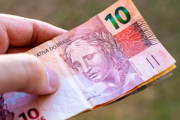Un homme tenant des factures du real brésilien