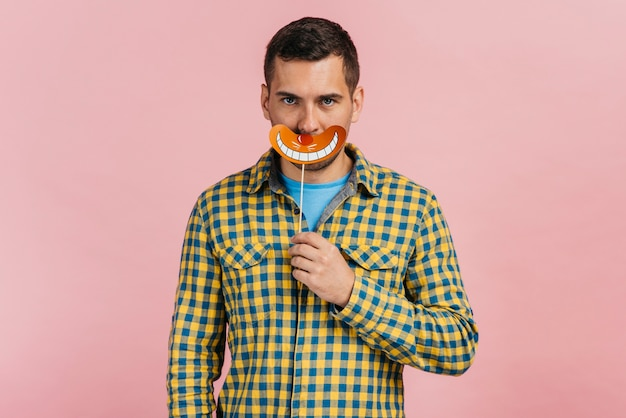 Homme tenant une fausse bouche avec un fond rose