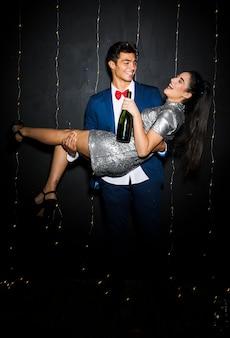 Homme tenant une femme souriante avec une bouteille