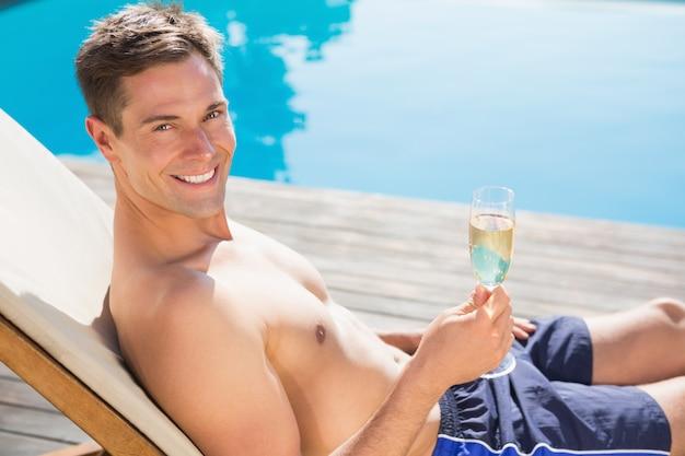 Homme tenant une flûte à champagne au bord de la piscine