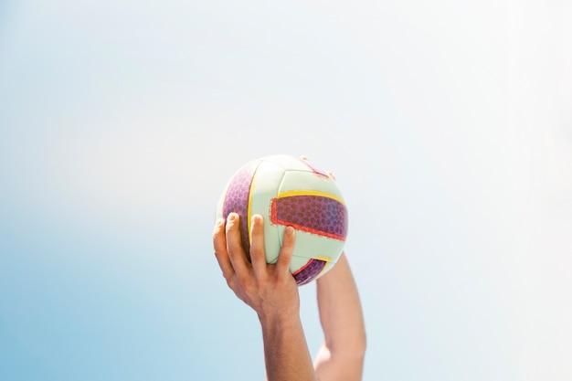 Homme tenant le football sur fond de ciel