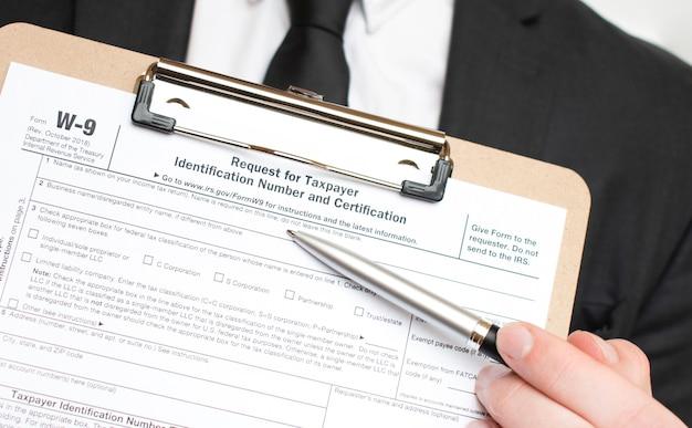 Homme tenant le formulaire fiscal américain w-9. document de loi de forme fiscale concept d'entreprise irs