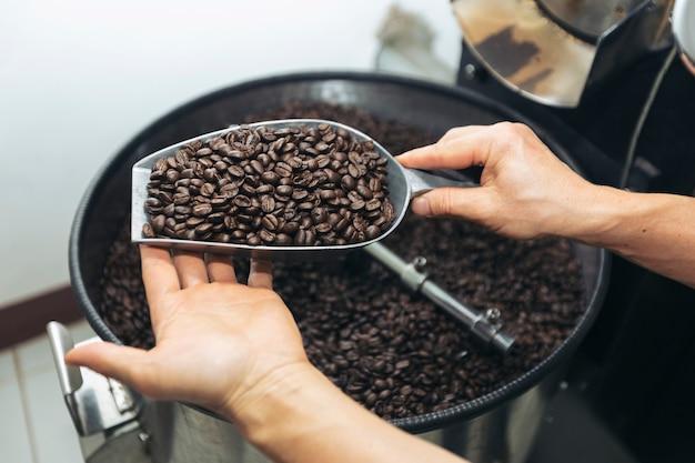 Homme tenant des grains de café à deux mains, vérifiant la qualité après torréfaction par machine moderne