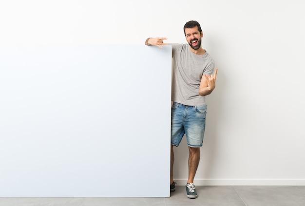 Homme tenant une grande pancarte vide bleue faisant un geste rock