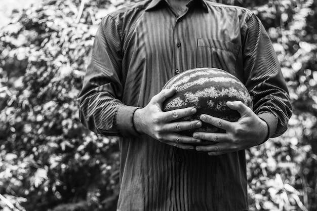 Un homme tenant une grosse pastèque mûre