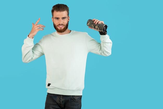 Homme tenant un haut-parleur sans fil écoutant de la musique isolée sur bleu