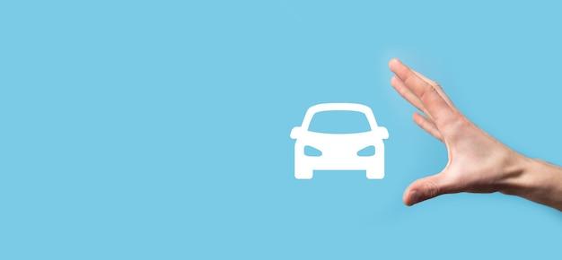 Homme tenant l'icône automatique de voiture sur la surface bleue.