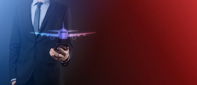 Homme tenant une icône d'avion avion dans ses mains. achat de billets en ligne. icônes de voyage sur le voyage