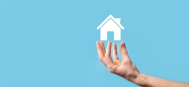 Homme tenant l'icône de la maison sur la surface bleue. concept d'assurance et de sécurité des biens concept immobilier.