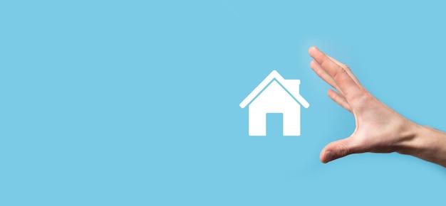 Homme tenant l'icône de la maison sur la surface bleue.
