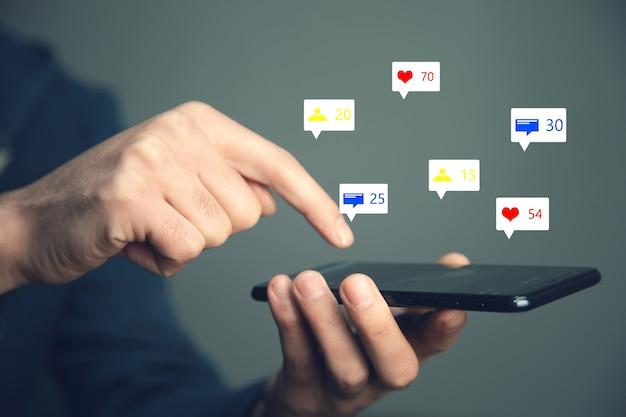 Homme tenant des icônes de médias sociaux avec téléphone intelligent