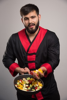 Homme tenant des légumes sur une poêle sombre.