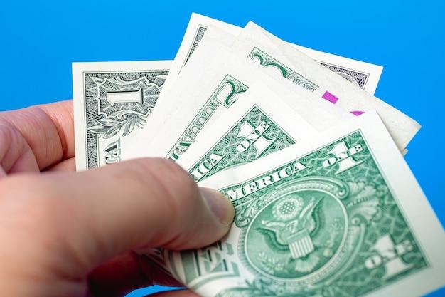 Un homme tenant une liasse de billets d'un dollar américain avec fond bleu