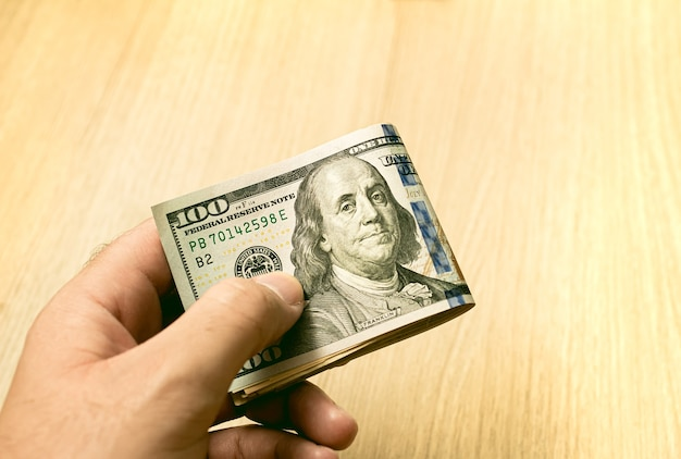 Un homme tenant une liasse de billets d'un dollar américain avec un fond en bois