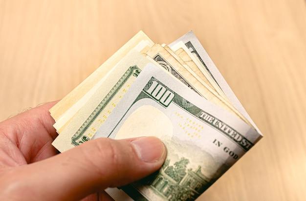 Un homme tenant une liasse de billets d'un dollar américain en photo gros plan avec fond en bois