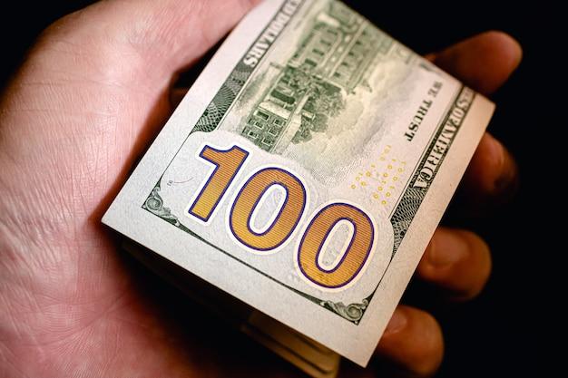 Un homme tenant une liasse de billets d'un dollar américain en photo gros plan avec fond noir