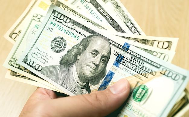 Un homme tenant une liasse de billets d'un dollar américain en photo gros plan
