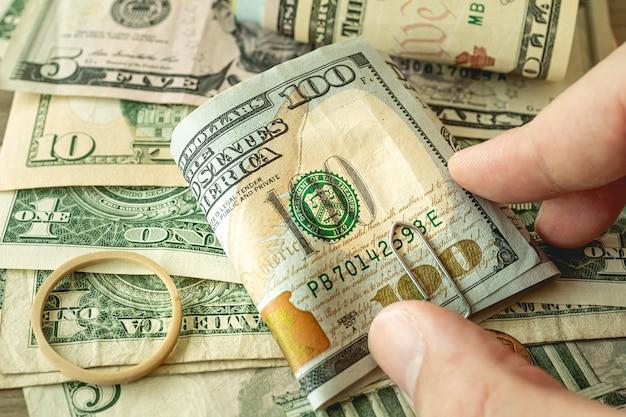 Un homme tenant une liasse de dollars des états-unis photo en gros plan