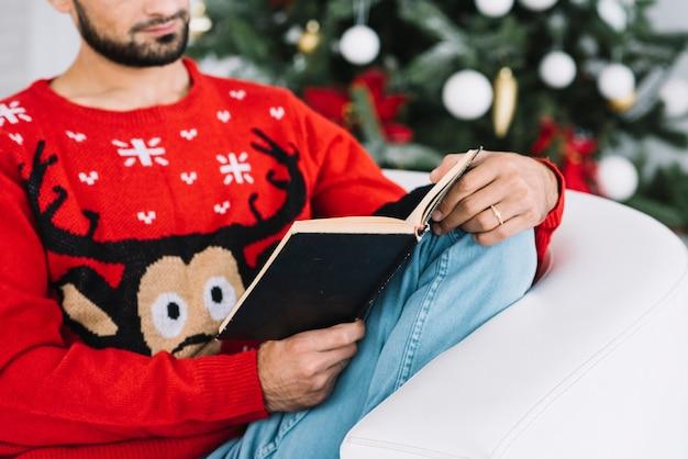 Homme tenant un livre sur un canapé