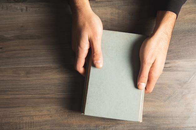 Homme tenant un livre à table. vue d'en-haut