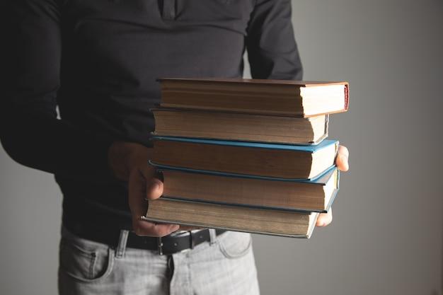 Homme tenant des livres dans ses mains sur fond gris