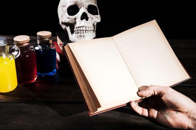 Homme tenant des livres sur fond avec des décorations d'halloween