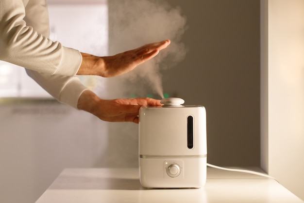Homme tenant la main sur le diffuseur d'huile d'arôme de vapeur sur la table à la maison, vapeur de l'humidificateur d'air