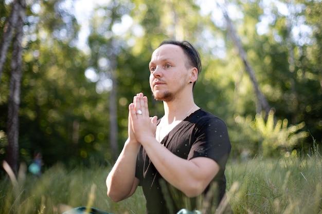 Homme tenant la main à namaste faisant du yoga dans le parc sur l'herbe verte. journée de la santé mentale