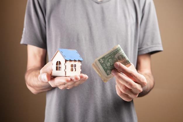 Un homme tenant une maison et de l'argent dans ses mains