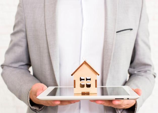Homme tenant une maison en bois sur une tablette