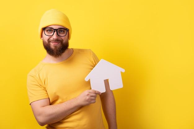 Homme tenant la maison sur fond jaune, concept de prêt hypothécaire