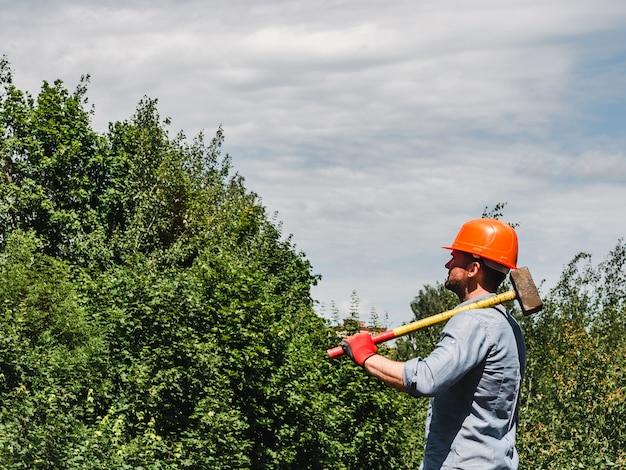 Homme tenant un marteau dans le parc
