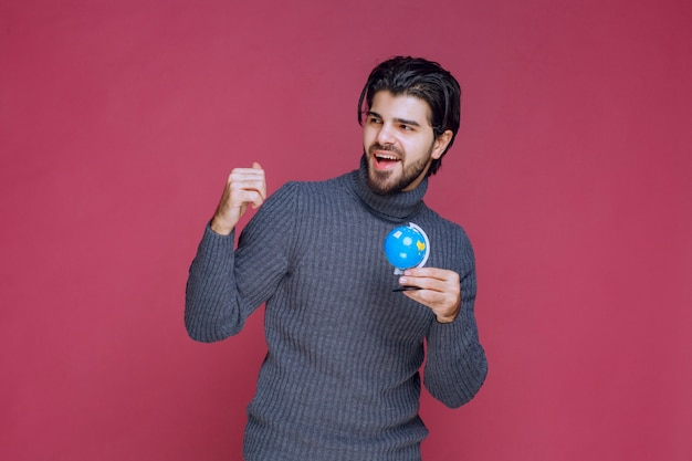 Homme tenant un mini globe bleu et le démontrant à la foule.