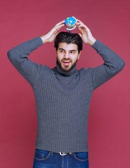 Homme tenant un mini globe entre les paumes.