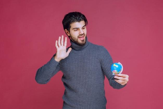 Homme tenant un mini globe et envoi de salutations.