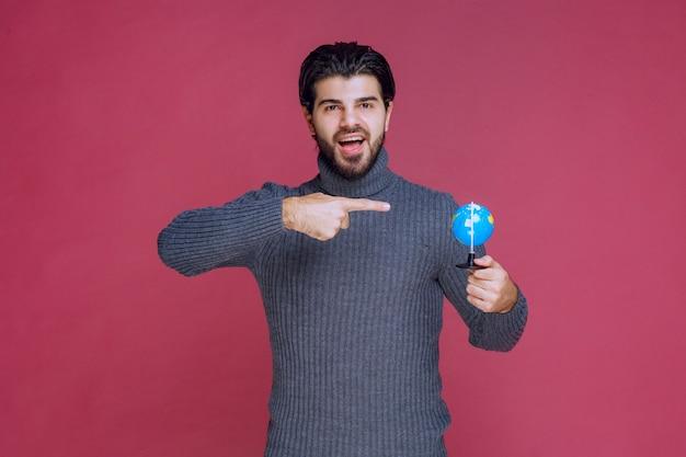Homme tenant un mini globe et faisant une présentation à ce sujet.