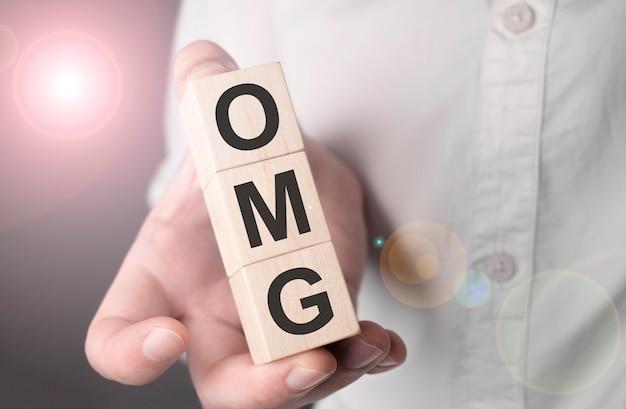 Homme tenant le mot omg sur cube en bois.