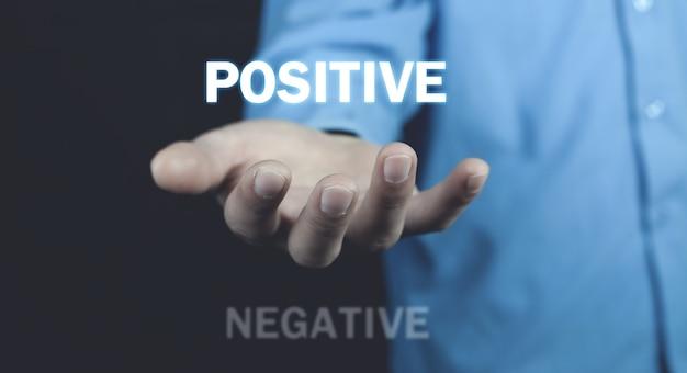 Homme tenant des mots positifs et négatifs. positif